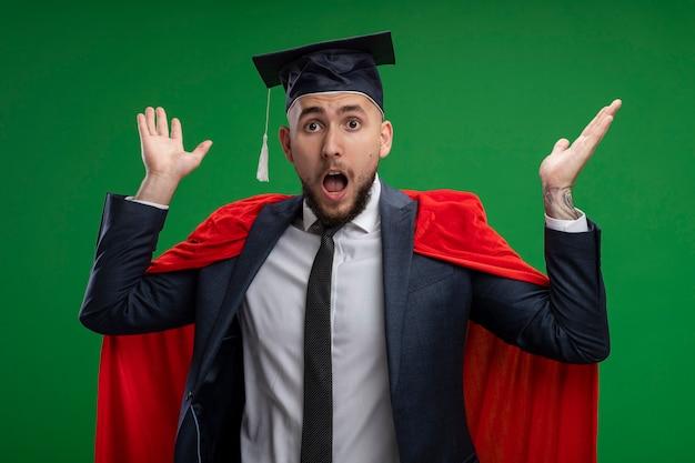 Absolwent w czerwonej pelerynie zdumiony i zdziwiony z podniesionymi rękami stojącymi nad zieloną ścianą