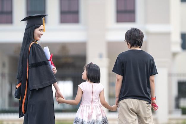 Absolwentka i rodzina świętują swoje osiągnięcie w nauce po ukończeniu studiów w dniu rozpoczęcia studiów