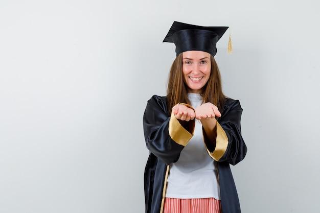 Absolwentka kobieta w ubranie, mundur odbierający lub dający gest i wyglądający wesoło, widok z przodu.