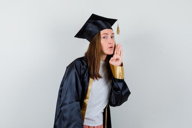 Absolwentka mówi tajemnicę za ręką w akademickim stroju i wygląda zaciekawiona. przedni widok.