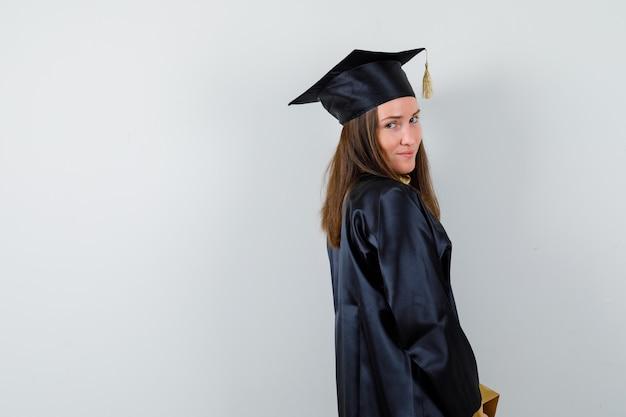 Absolwentka patrząc na kamery w stroju akademickim i wyglądająca rozsądnie.