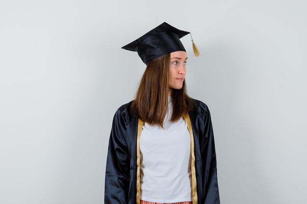 Absolwentka patrzy na bok w zwykłym ubraniu, mundurze i wygląda na skupioną. przedni widok.