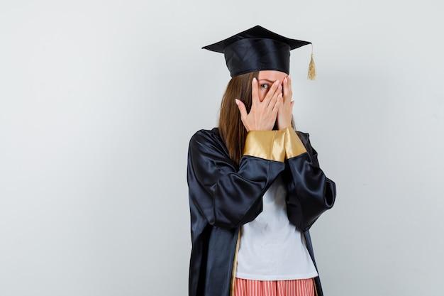 Absolwentka patrzy przez palce w zwykłym ubraniu, mundurze i wygląda na przestraszoną. przedni widok.