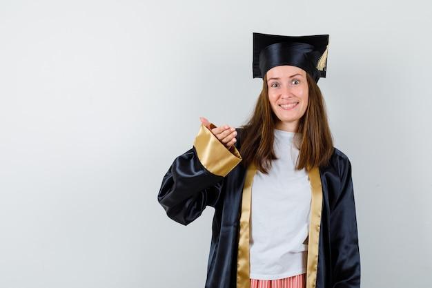 Absolwentka podnosząca rękę, aby pokazać coś w akademickim stroju i wesoło wyglądająca, widok z przodu.