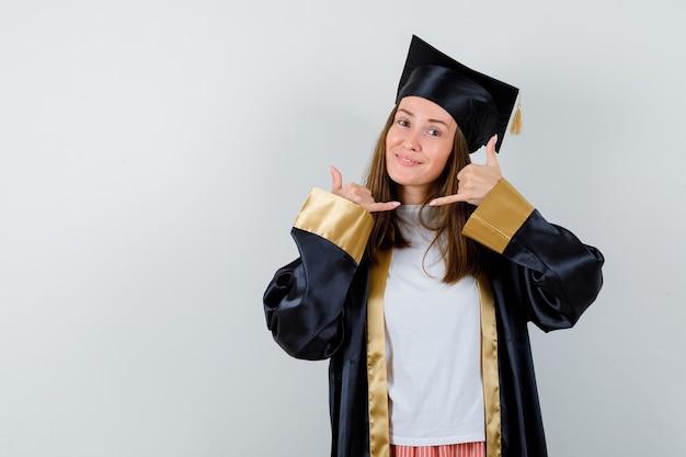 Absolwentka pokazując gest telefonu w akademickim stroju i patrząc wesoło. przedni widok.