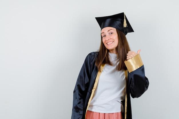 Absolwentka pokazuje kciuk w akademickim stroju i wygląda na szczęśliwego. przedni widok.