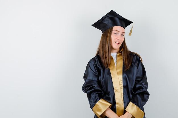 Absolwentka pozowanie stojąc w akademickim stroju i patrząc pewnie, widok z przodu.