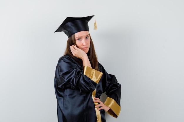 Absolwentka pozowanie stojąc w akademickim stroju i patrząc wdzięcznie. przedni widok.