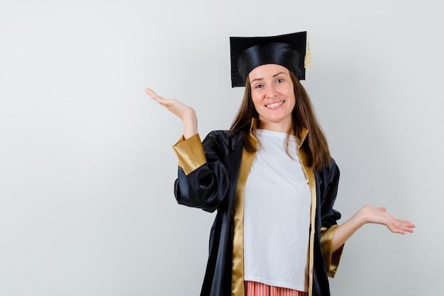 Absolwentka robi gest wagi w akademickim stroju i szuka wesołej. przedni widok.