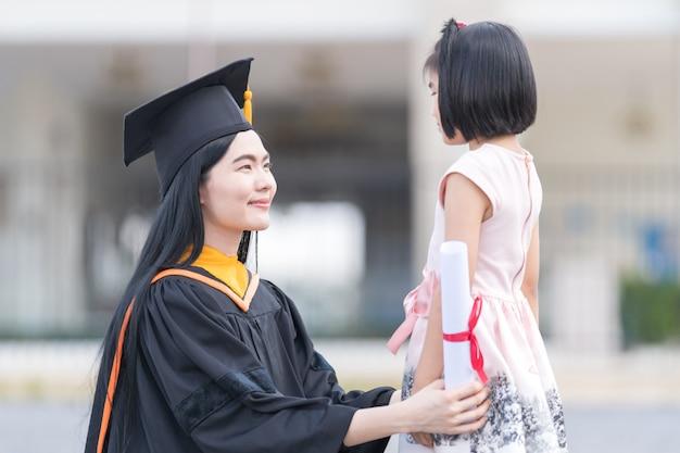 Absolwentka studiów z małą dziewczynką w dniu ukończenia szkoły