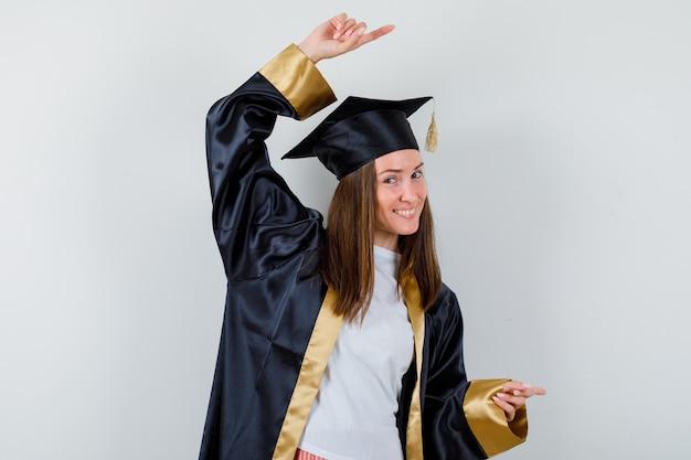 Absolwentka w akademickim stroju, wskazując w prawo i patrząc wesoło, widok z przodu.