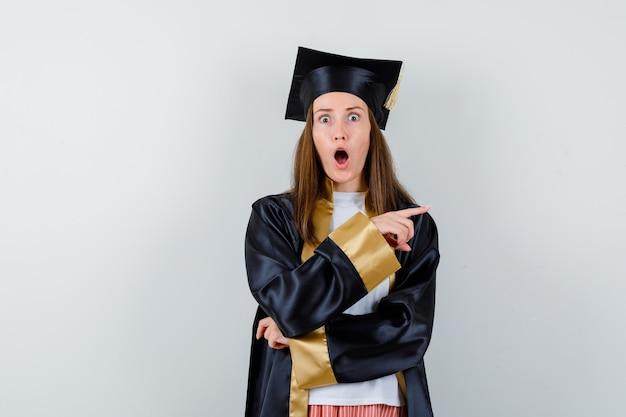 Absolwentka w akademickim stroju, wskazując w prawo i patrząc zdziwiony, widok z przodu.
