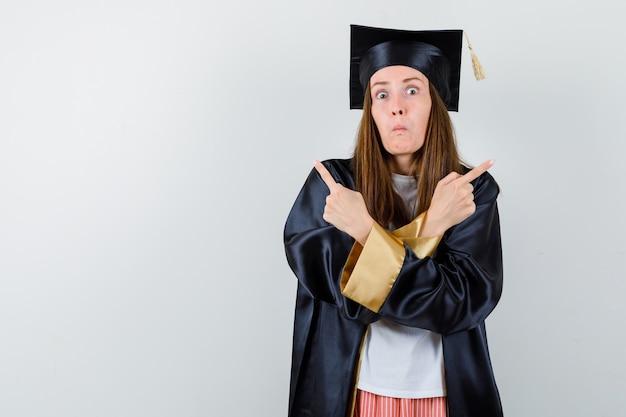 Absolwentka w zwykłym ubraniu, mundurek skierowany w górę i zdziwiony, widok z przodu.