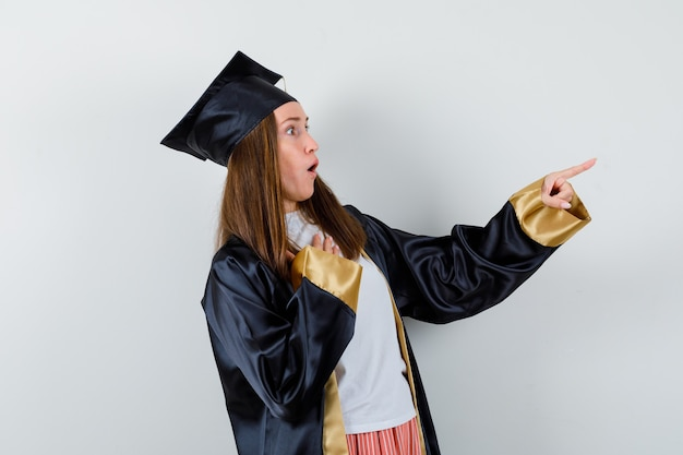 Absolwentka wskazując w prawo w akademickim stroju i patrząc przestraszony, widok z przodu.
