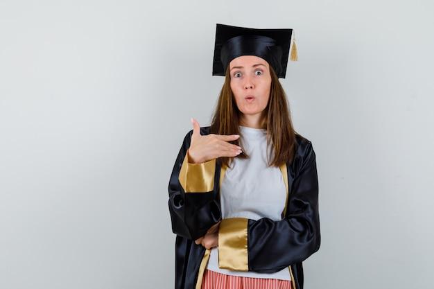 Absolwentka wskazująca na siebie w zwykłym ubraniu, mundurze i wyglądająca na zaskoczoną. przedni widok.