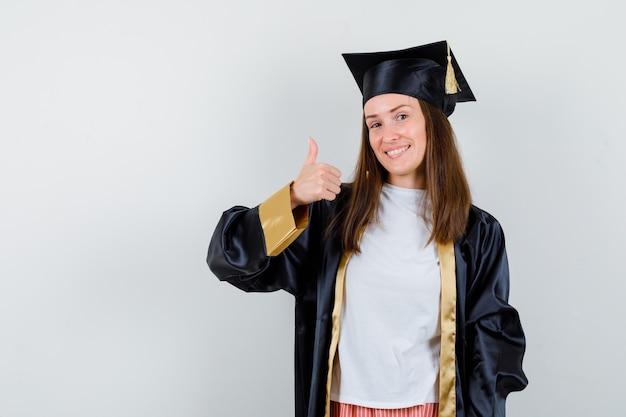 Absolwentka wyświetlono kciuk w akademickim stroju i patrząc wesoły, widok z przodu.