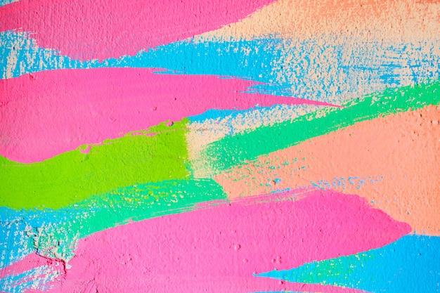 Abstrakcjonistyczna tekstura tynku z falistych linii z pędzla w kolorze różowym, niebieskim, zielonym i beżowym.