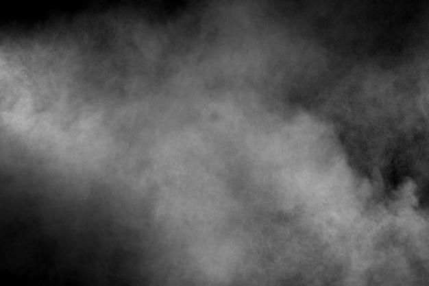 Abstrakcjonistyczny białego proszka wybuch na czarnym tle