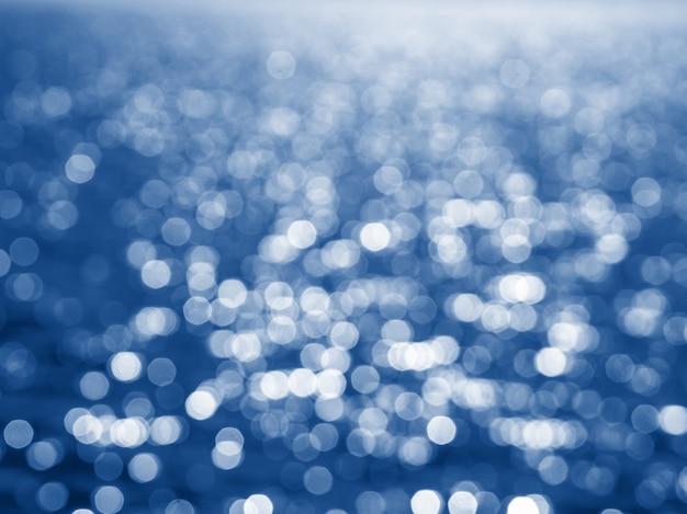 Abstrakcjonistyczny błękit okrąża bokeh na boże narodzenia jakaś tło, defocused. miękkie kolorowe rozmyte i świecące światła modne klasyczny niebieski kolor roku 2020