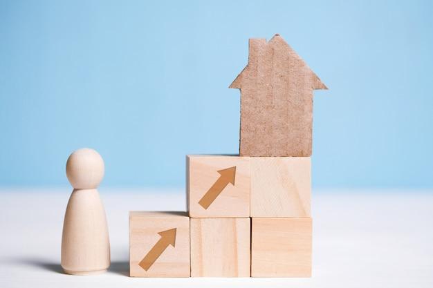 Abstrakcjonistyczny kartonu dom na drewnianych sześcianach i mężczyzna. kupno domu jako cel.