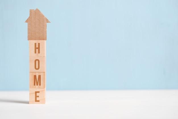 Abstrakcjonistyczny kartonu dom na drewnianych sześcianach z inskrypcją