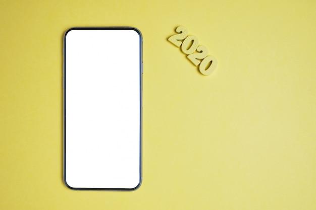 Abstrakcjonistyczny rok 2020 drewniani listy obok smartphone na żółtym tle.