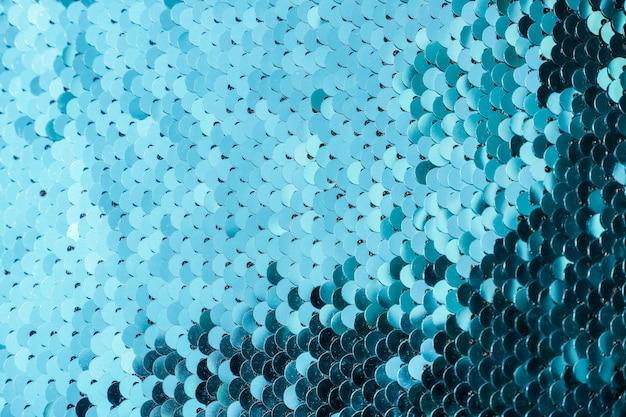 Abstrakcjonistyczny tło z błękitnymi cekinami barwi na tkaninie. skale tekstur okrągłych cekinów z przejściem kolorów.