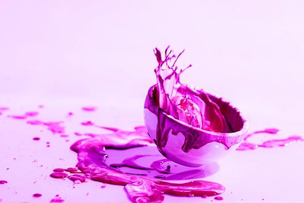Abstrakcjonistyczny tło z różowym farby pluśnięciem i filiżanką