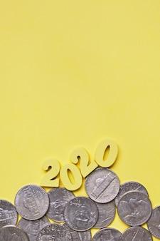 Abstrakcjonistyczny wizerunek 2020 drewniane postacie i monety centy na żółtym tle. widok z góry. pionowy. skopiuj miejsce