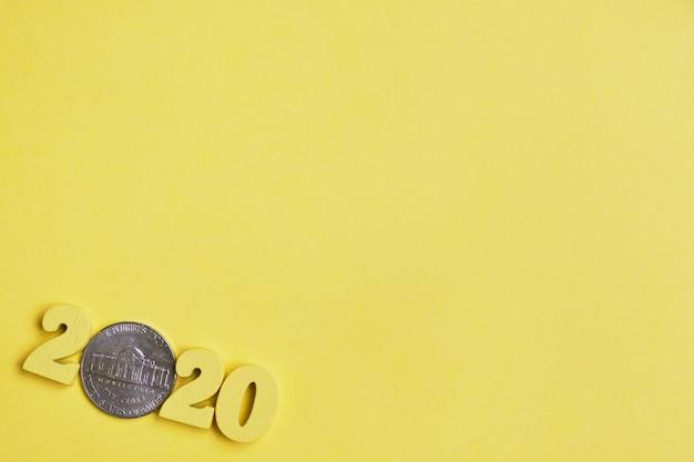 Abstrakcjonistyczny wizerunek 2020 drewniane postacie i monety centy na żółtym tle. widok z góry. skopiuj miejsce
