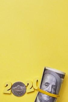 Abstrakcjonistyczny wizerunek 2020 drewnianych figurek i monet centów blisko rolki dolary wiązanej elastycznym bandonem na żółtym tle.
