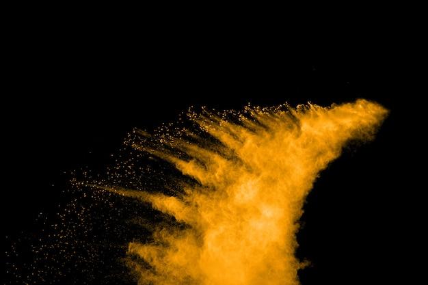 Abstrakcjonistyczny wybuch pomarańczowy pył na czarnym tle.