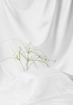 Abstrakcyjna biała satyna jedwabista tkanina na tło, tkanina tekstylna z fałdami falistymi fałdami. z miękkimi falami, macha z kwiatami trawy