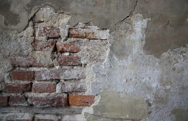 Abstrakcyjna część starego ceglanego muru ze zniszczonym tynkiem na vintage tło i tapetę w stylu sepii