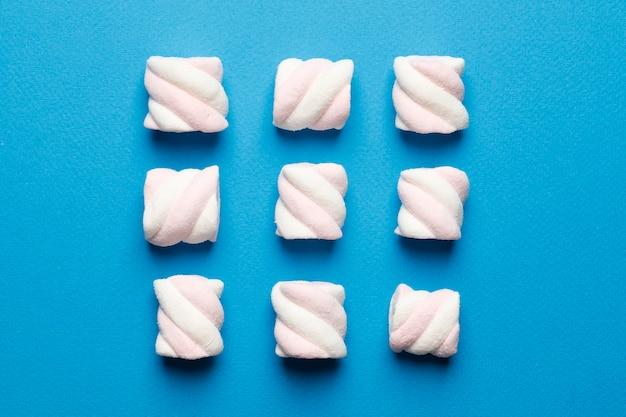 Abstrakcyjna kompozycja marshmallows na niebieskim tle. widok tov