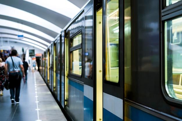 Abstrakcyjna nowoczesna stacja metra z tłumem ludzi i zamykaniem drzwi