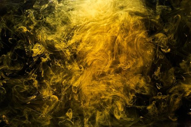 Abstrakcyjna płynna sztuka, żółta bomba dymna na czarnym tle, bursztynowe farby akrylowe pod wodą