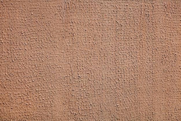 Abstrakcyjna powierzchnia tynku szorstkiego pomarszczona, pomalowana na kolor brązowy.