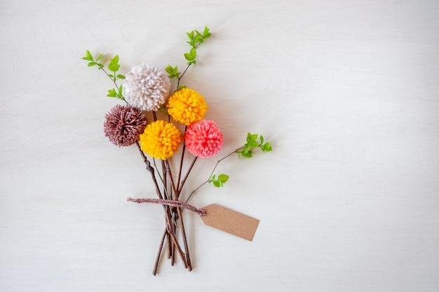 Abstrakcyjne bukiety kwiatów wykonane z kolorowych pomponów.
