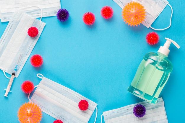 Abstrakcyjne modele wirusa z maskami medycznymi, strzykawką i środkiem dezynfekującym do rąk na niebieskim tle