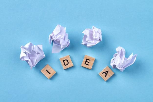 Abstrakcyjne pojęcie idei. idea słowo napisane drewnianymi klockami. na białym tle na niebieskim tle.