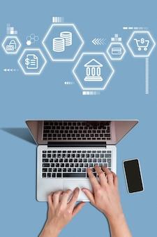 Abstrakcyjne rodzaje usług bankowości mobilnej są oglądane przez osobę korzystającą z laptopa.