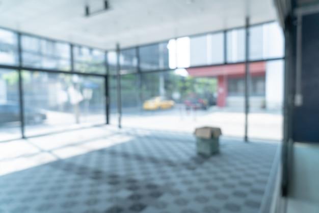 Abstrakcyjne rozmycie puste biuro ze szklanym oknem i światłem słonecznym w tle