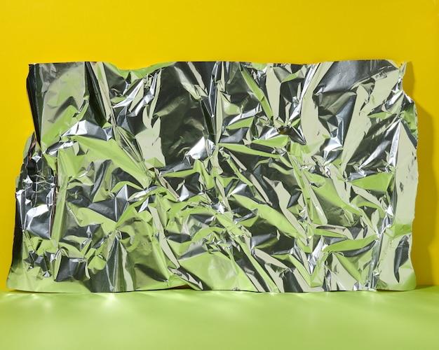 Abstrakcyjne tło do demonstracji produktu, zmięta folia z zielonym odbiciem, puste