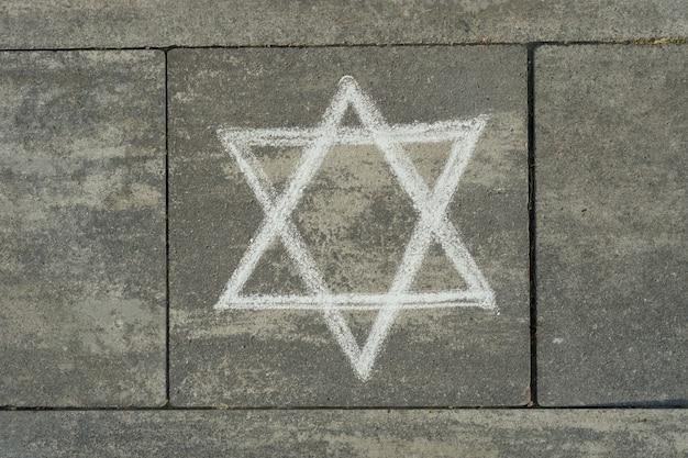 Abstrakcyjny obraz sześcioramiennej gwiazdy, napisany na szarym chodniku