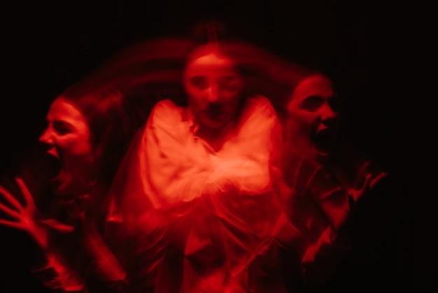 Abstrakcyjny, rozmyty portret kobiety psychotyka z zaburzeniami afektywnymi dwubiegunowymi i schizofrenicznymi z czerwonym podświetleniem na czarnym tle