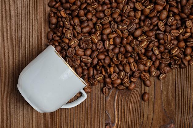 Abstrakcyjny strumień ziaren kawy wykonany z białej filiżanki na drewnianym stole