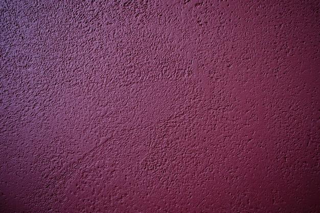 Abstrakta wzór betonowy bordowy kolor. malowana tynkowana ściana. grunge dekoracyjny blady.