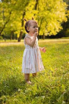 Aby dziewczynka dobrze się bawiła w parku, biegając boso po zielonej trawie.