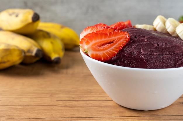 Acai, brazylijska miska do lodów mrożonych jagód acai z truskawkami i bananami. z owocami na drewnianym stole. widok z przodu menu letniego
